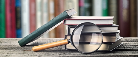 Image of books and magnifying glass